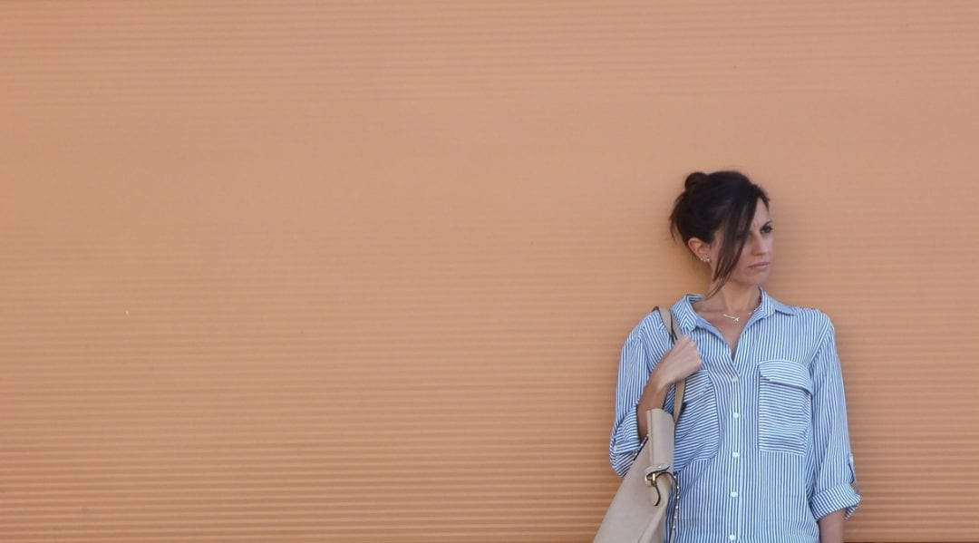mujer con look sport y camisa de rayas